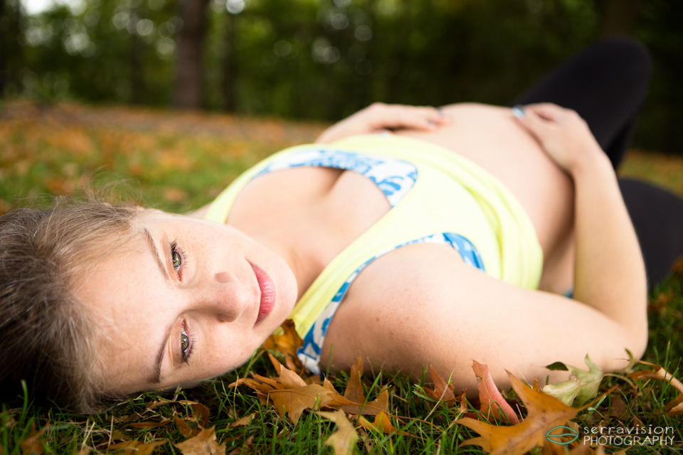 Active mom-to-be rests in the grass at Willamette Park after yoga in the park in Portland, Oregon