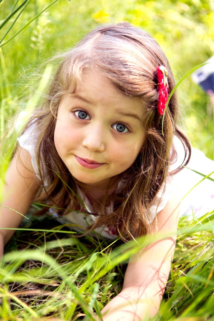 young girl lying in the grass with a sassy expression that really shows her personality