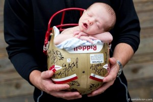 Newborn photo in a football helmet