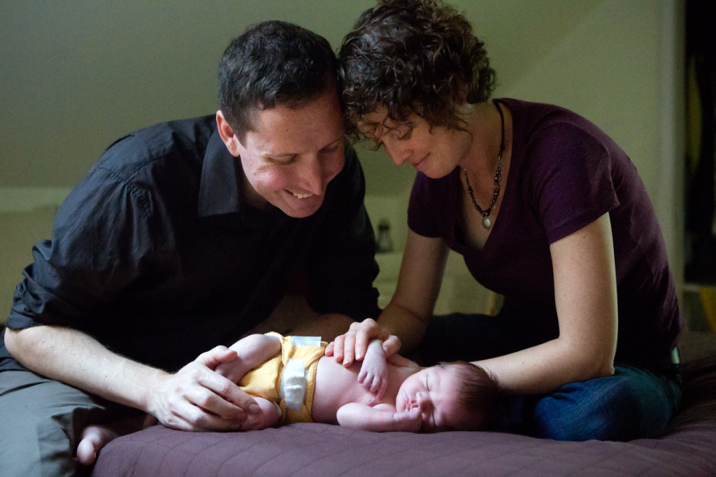 professional photo of parents with newborn baby on bed