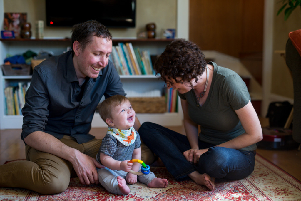 Photo of my husband and I playing and laughing with our son at 6 months old