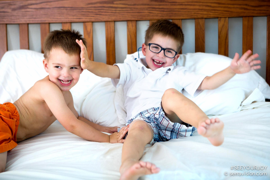 A photo of two toddler boys, brothers, 2 and 3 years old, rough housing on mom and dad's bed and laughing
