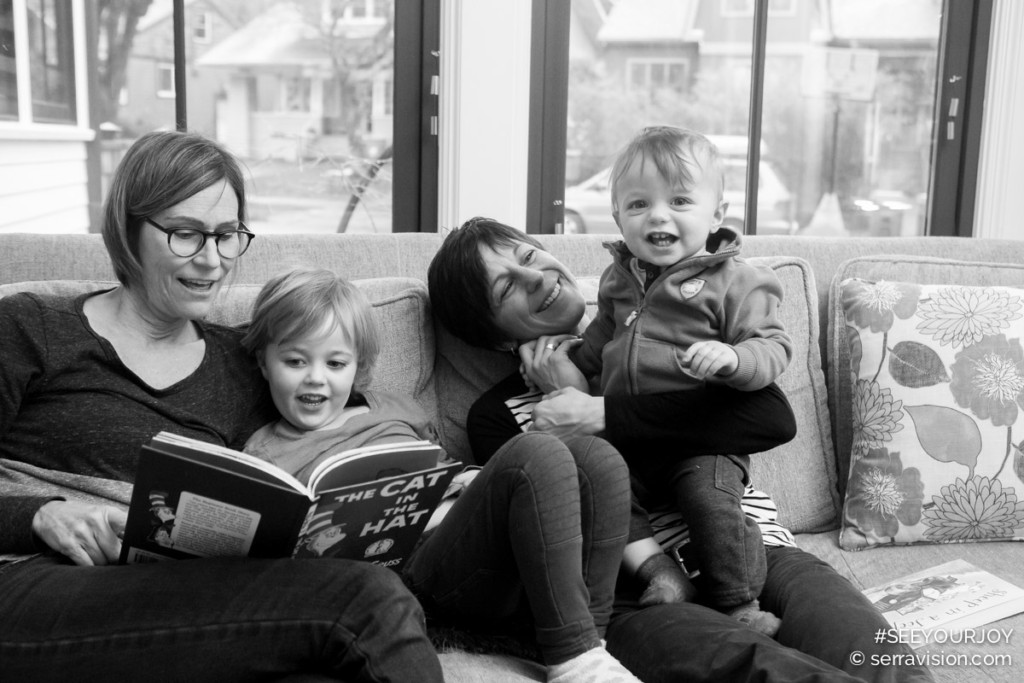 "two moms reading ""The Cat In The Hat"" with their two kids, a 3-yar-old girl and baby boy. They are all smiling and so happy together!"