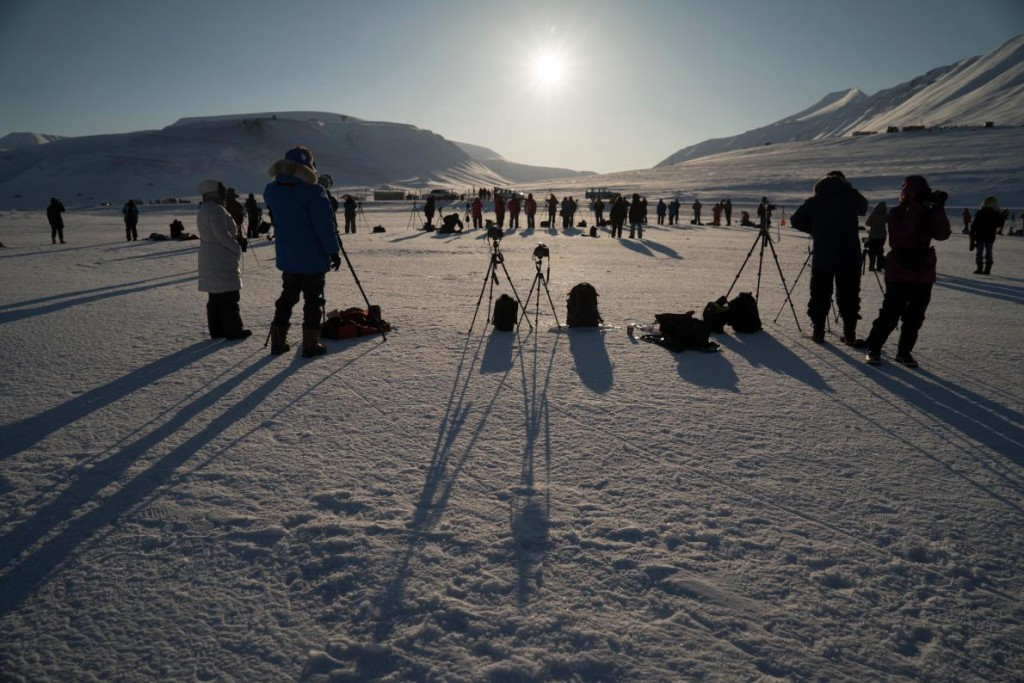 Image of many people standing in silhouette watching a solar eclipse on an icy tundra near the North Pole