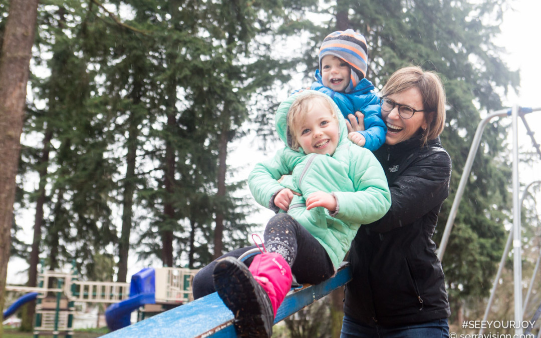 mom plays on a see-saw with her two kids, a 3-yar-old girl and baby boy. They are all laughing and so happy together!