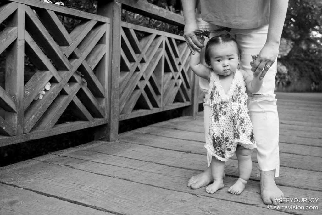 one year old baby is holding her mom's hands while she stands on a bridge in the crystal springs rhododendron garden