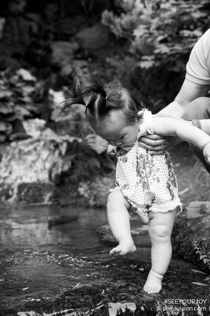 one year old baby touches her feet to the cold water for the first time at crystal springs rhododendron garden