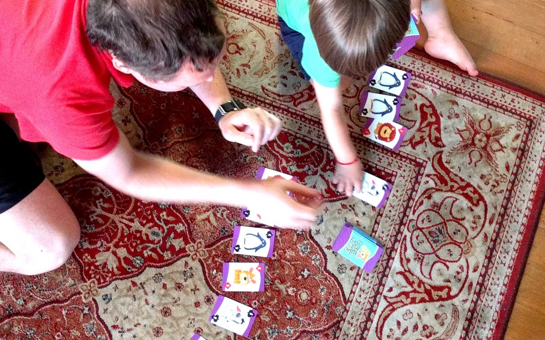 This picture shows a 2-year-old and his dad lining the cards up on the floor together